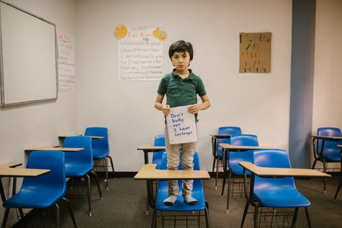 Boy Standing on Blue Chair While Holding a Message Against Bullying