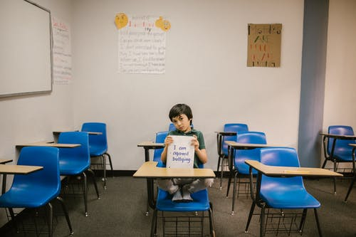 Boy Sitting on Blue Chair While Holding a Message Against Bullying