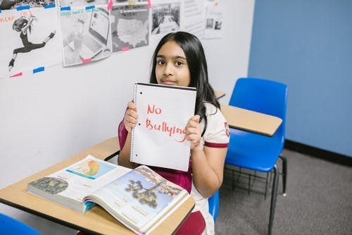 Girl Showing a Message Written in a Notebook