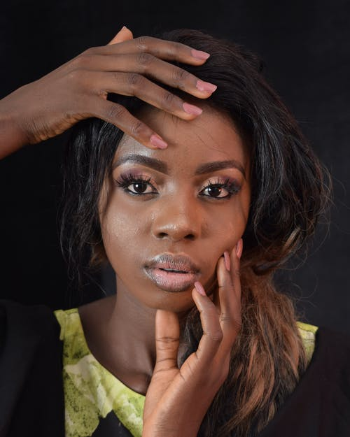 Pensive African American female with dark hair in casual clothes touching face and looking at camera against dark background
