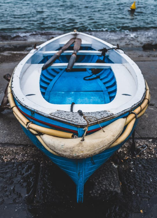 White and Blue Wooden Boat on Seashore