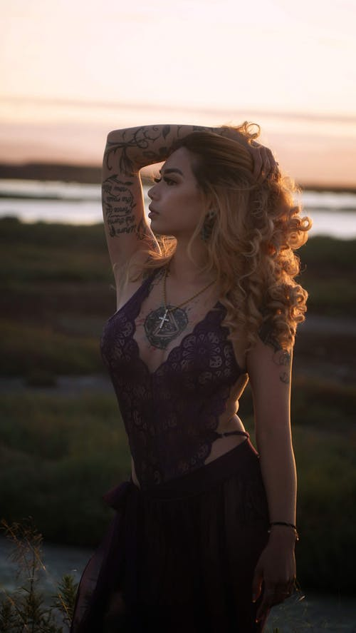 Peaceful ethnic female with hand on head and tattoos standing against river at sunset and looking away
