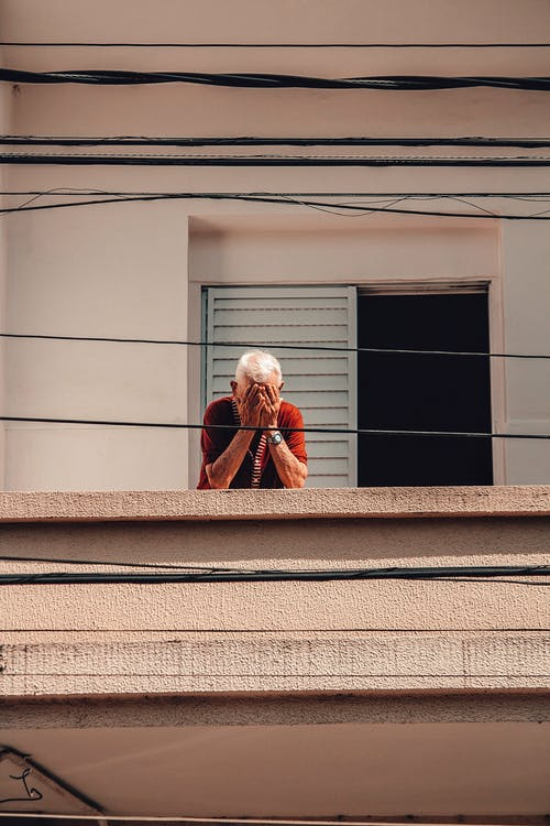 From below of gray haired anonymous senior male standing on balcony and covering face with hands