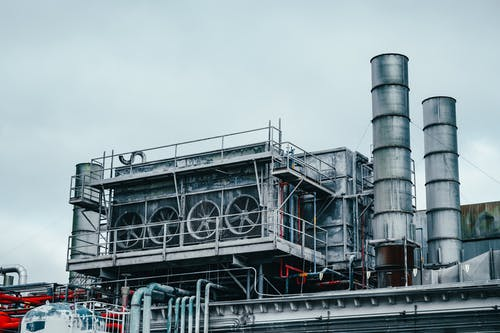 Exterior view of large industrial construction with metal tubes located on factory in daytime on cloudy weather