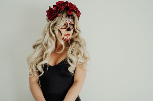 Gorgeous young female with long blond hair in black dress with Mexican Catrina inspired makeup and floral headband standing against white background and looking away