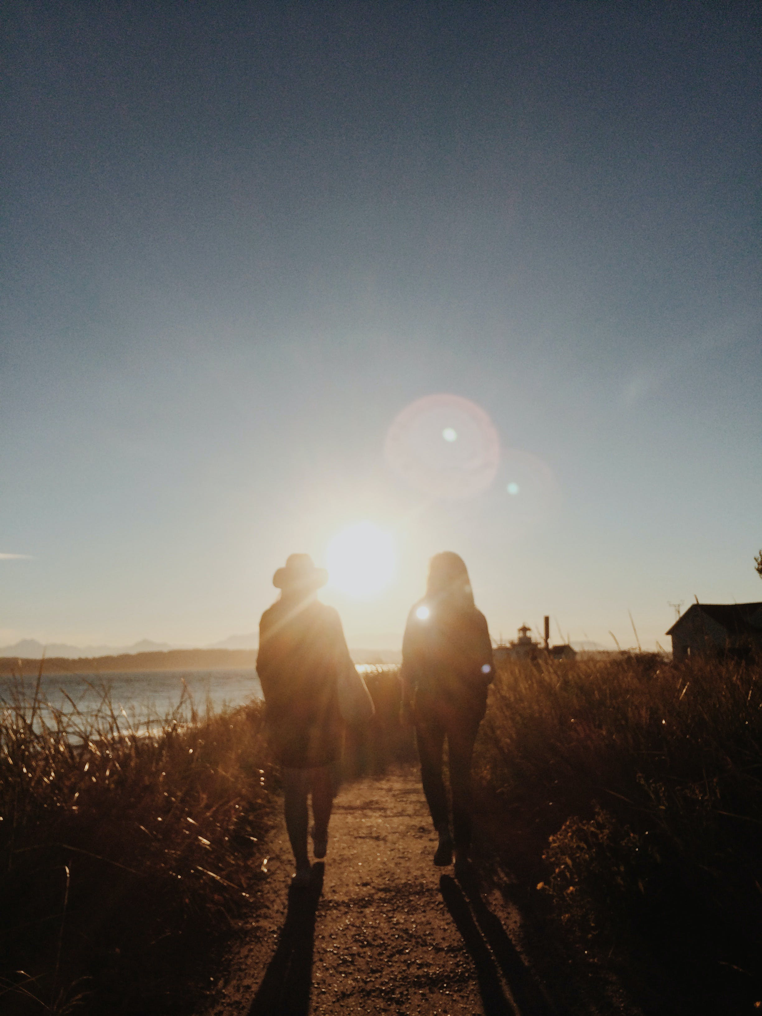 Silhouette of Two People Walking Near Body of Water during Golden Hour