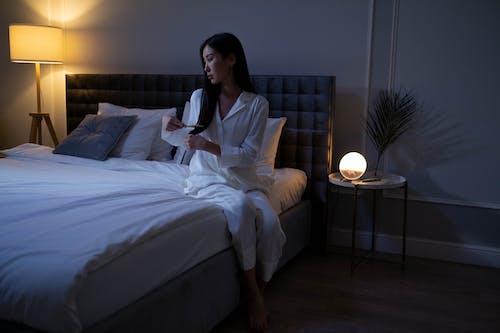Woman in White Pajamas Brushing Her Hair