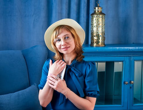 Smiling woman in eyeglasses and hat near blue armchair
