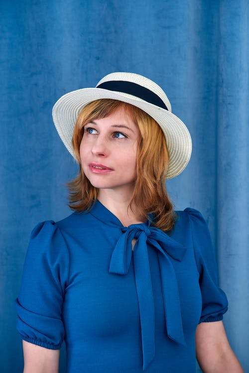 Charming female model with wavy hair wearing blue dress and hat looking away dreamily