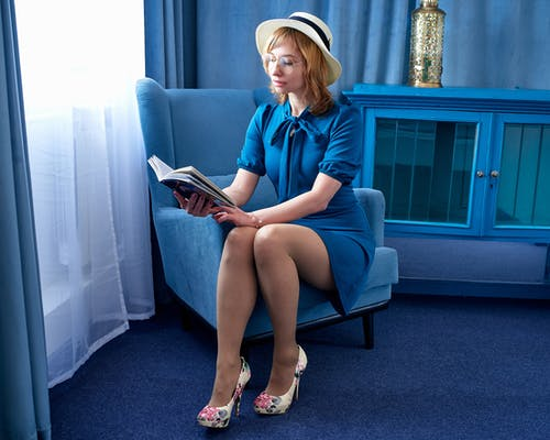 Woman on armchair with book near cabinet in room