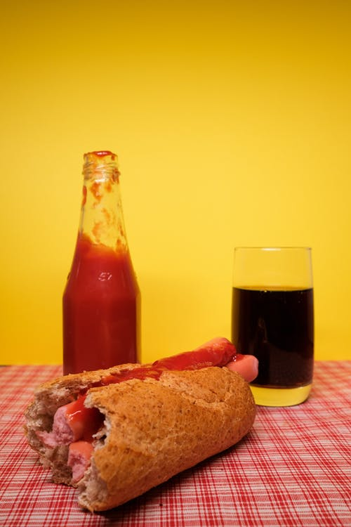 Appetizing homemade hot dog placed on table with bottle of ketchup and glass of coke against yellow background