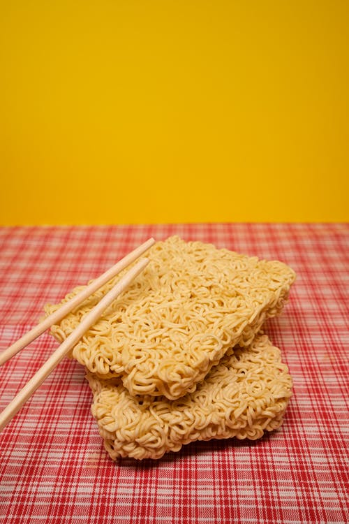 Dried instant noodles with chopsticks placed on table in kitchen