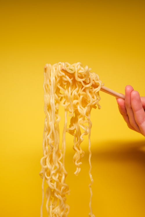 Crop anonymous person holding instant noodles with bamboo chopsticks against yellow background