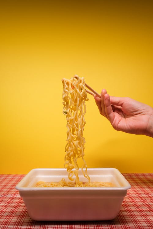 Crop anonymous person using bamboo chopsticks while eating traditional instant noodles prepared in container in kitchen