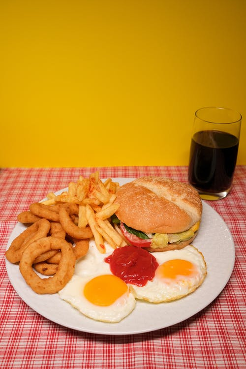 Plate with assorted fast foods served on table with glass of coke