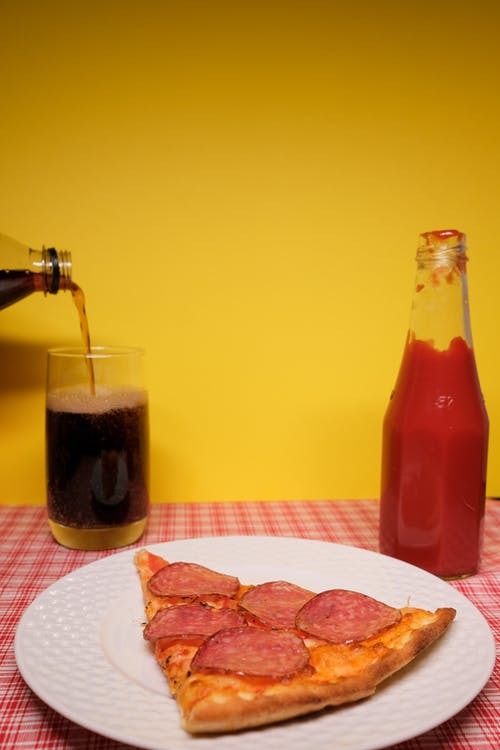 Plate of pizza served on table with ketchup and soft drink
