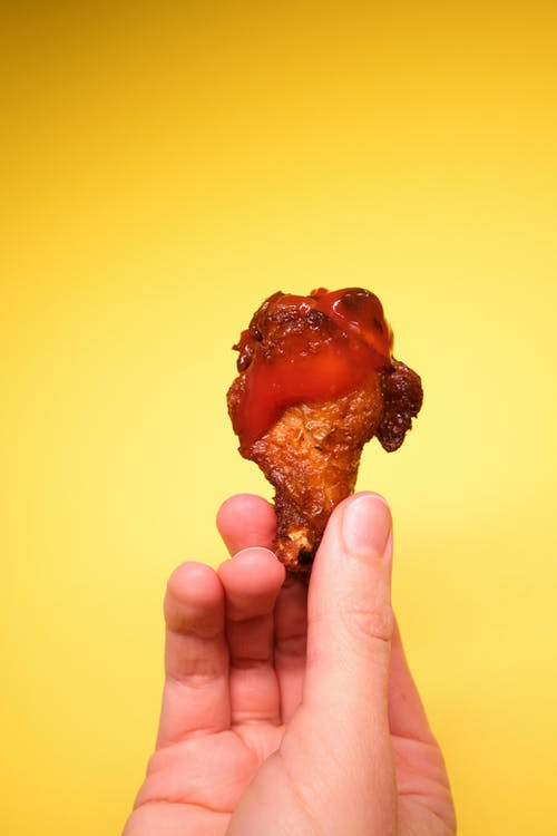 Anonymous person demonstrating fried chicken with ketchup in hand
