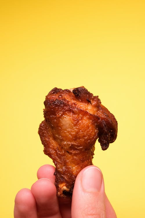 Crop faceless person with tasty fried chicken in hands on yellow background in light studio