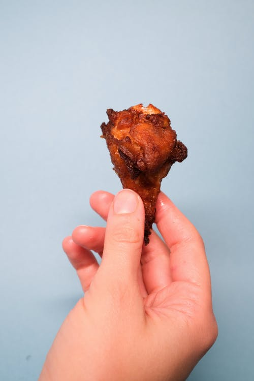 Anonymous person showing fried chicken in hand