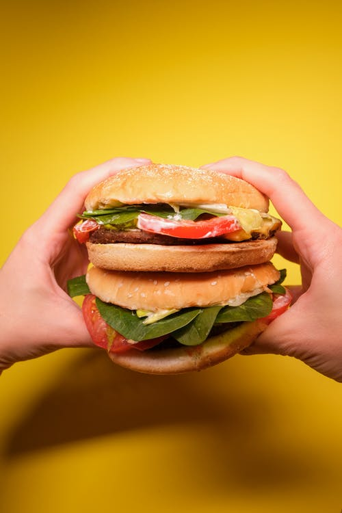 Person Holding Burger With Lettuce and Tomato
