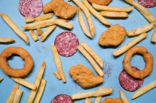 Salami with onion rings and nuggets near french fries