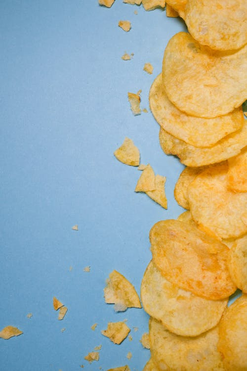 Top view of tasty golden potato chips on blue surface in light studio