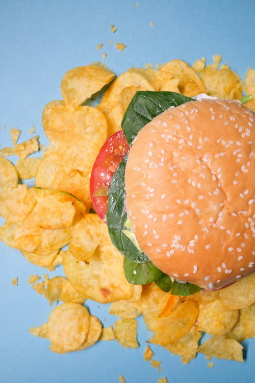 Burger with tomatoes on chips on blue table