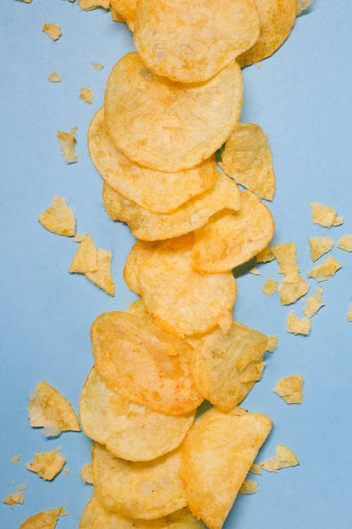 Top view of golden potato crisps placed on blue background in bright studio