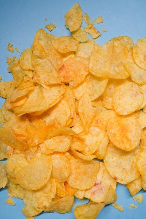 Crispy chips in studio on blue surface