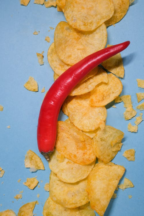 Top view of red hot chili pepper on golden crisps on blue background in bright studio