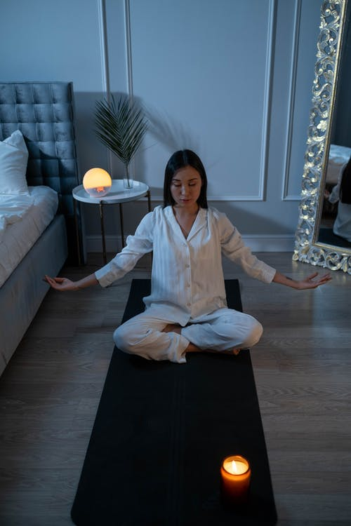 Woman in White Pajamas Meditating on a Yoga Mat