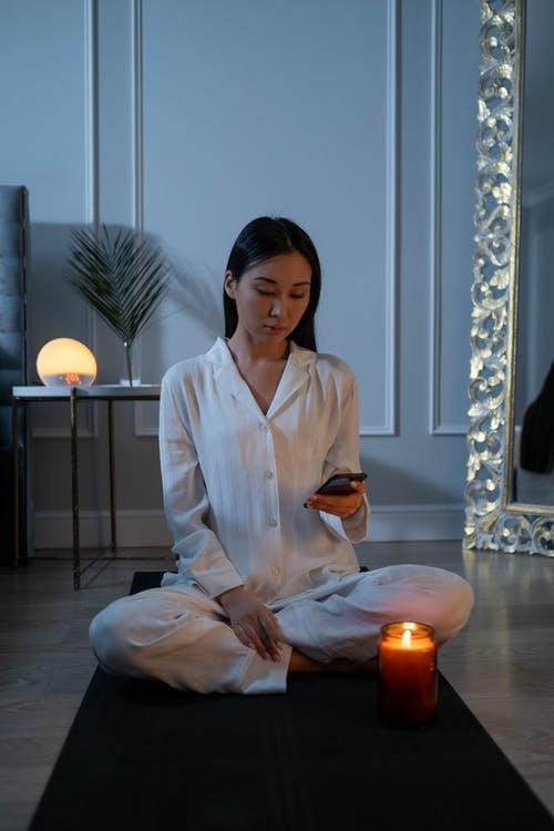 Woman in White Pajamas Sitting on a Yoga Mat Using Her Cell Phone