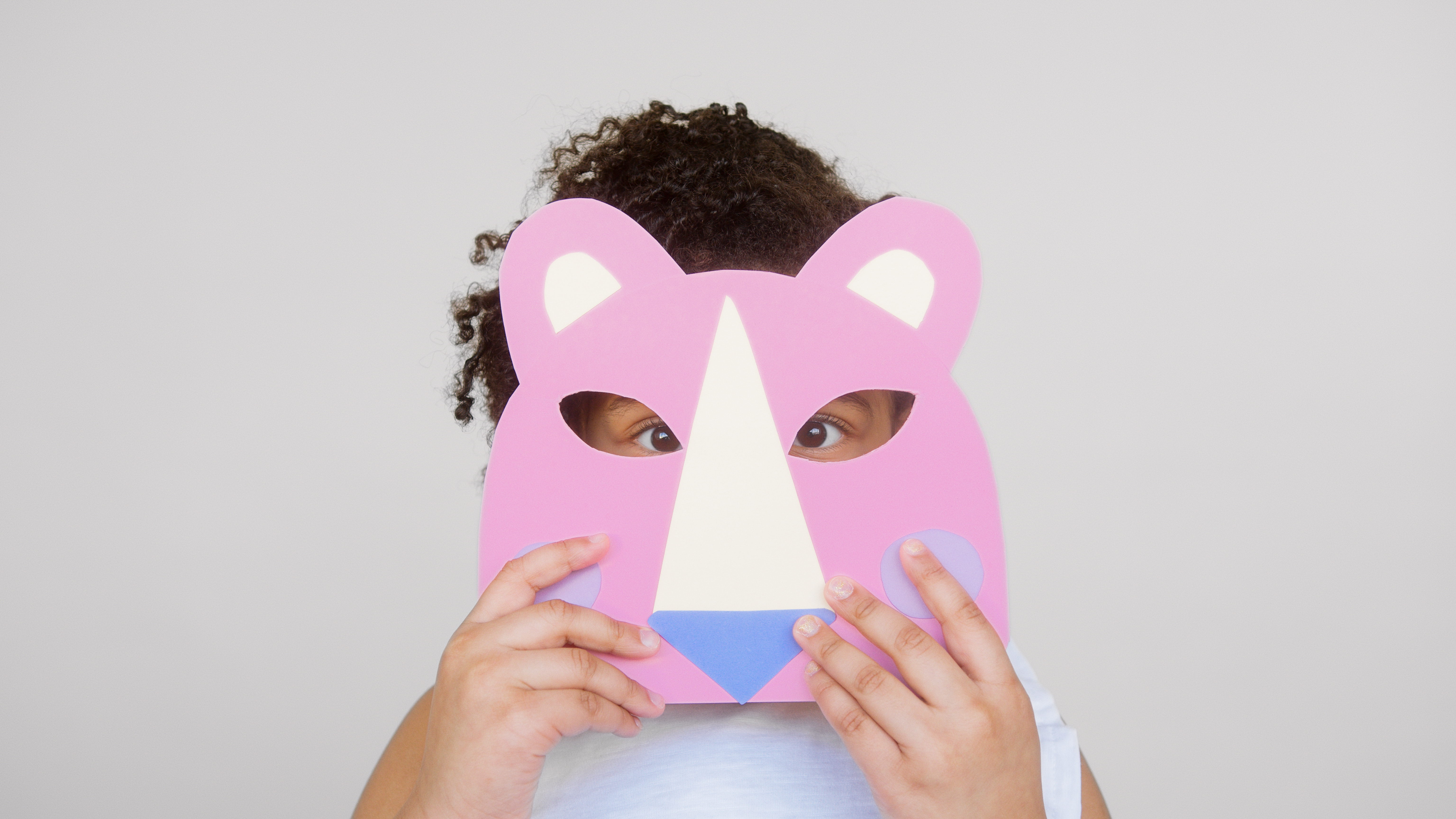 girl covering her face with a cutout animal mask