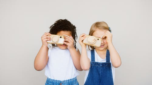 Two Kids Taking Photo Using a Camera