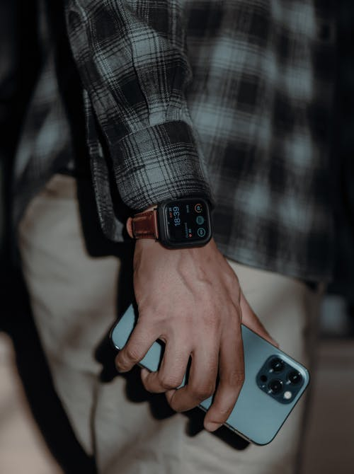 Side view of crop unrecognizable man in casual clothes and electronic wristwatch holding modern smartphone in sunlight