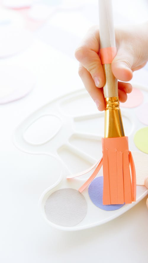 Close-Up View of a Kid Holding a Paintbrush
