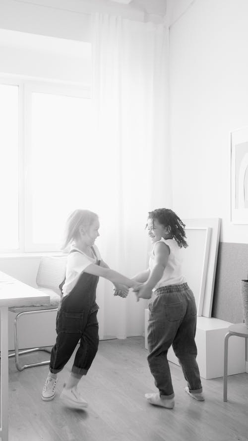 Monochrome Photo of Two Girls Playing