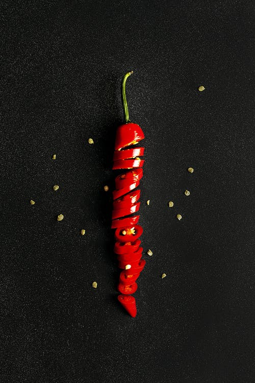 Sliced red chili pepper on black surface