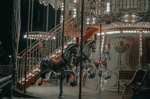 Glowing carousel with white horses and stairs with railing with ornamental elements at funfair at night
