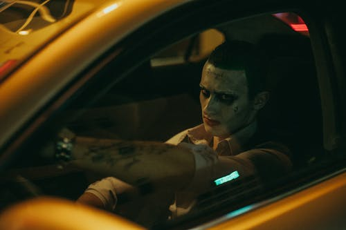 Confident male cosplayer with tattoos sitting in yellow automobile in city street while looking at camera at night