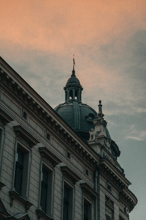 From below of aged buildings near cathedral with dome under blue cloudy sky in city street in twilight