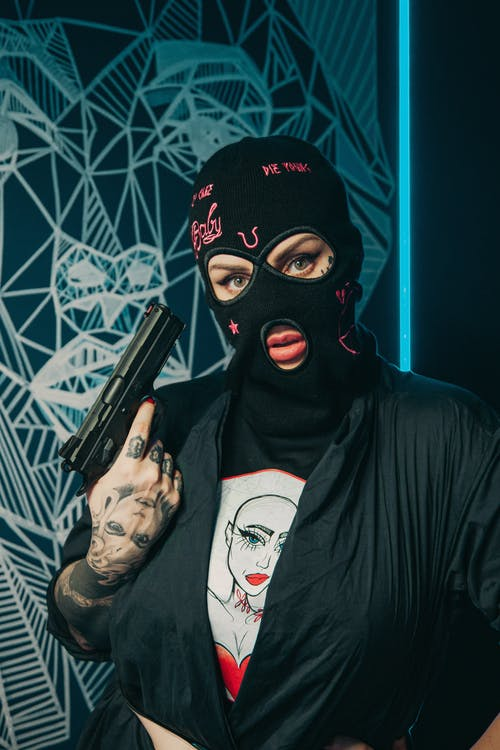 Lady burglar in mask with gun and tattoos