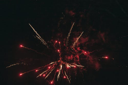Breathtaking view of illuminated red and golden fireworks bursting into dark cloudless sky at night