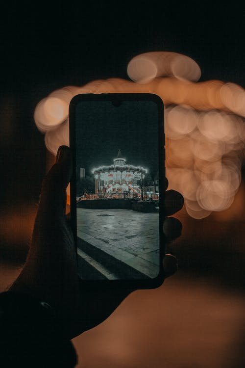 Crop person taking photo of attraction in darkness