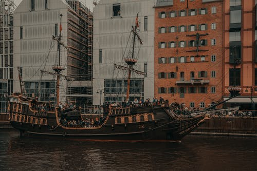 Old ship sailing on river near residential buildings in city