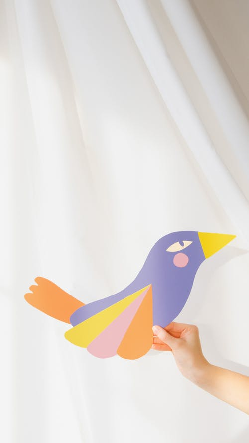 Person Holding a Colorful Paper Bird
