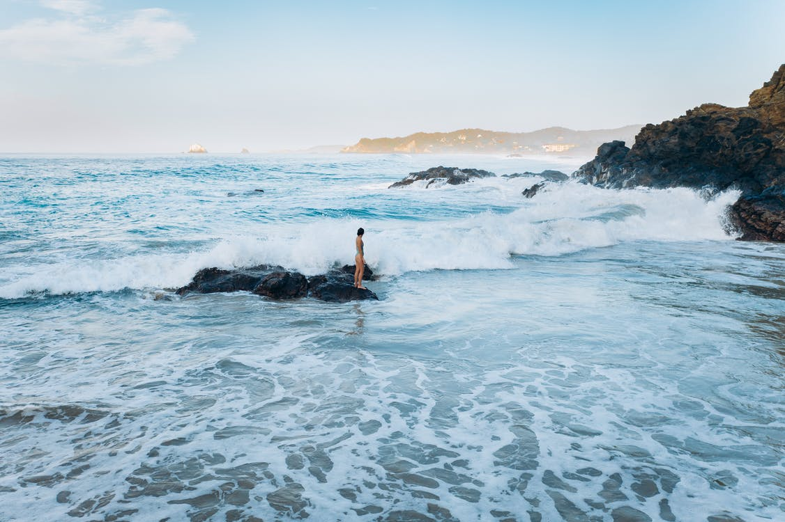 Person in Black Wetsuit Surfing on Sea Waves