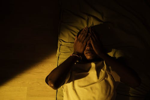 A Man Lying on the Bed in a Dark Room