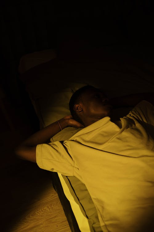 A Man in White Shirt Lying on the Bed in a Dark Room