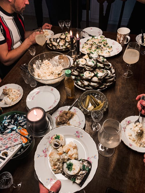 From above of unrecognizable people sitting at festive table with assorted dishes while having dinner during holiday celebration at home